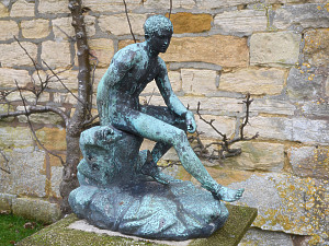 A Neapolitan verdigris bronze of the seated Mercury on a stylised rock
