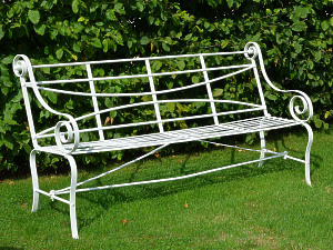 A 19th century wrought iron strap work garden seat having cabriole legs and scroll arms