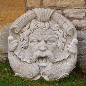 A carved weathered natural limestone fountain mask in the form of a river god