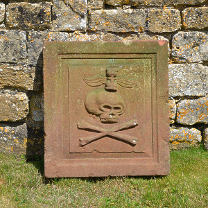 An 18th century sandstone plaque showing a skull and crossbones