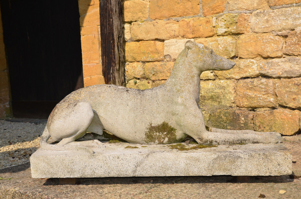 A large pair of composition stone reclining greyhounds by Austin and Seeley