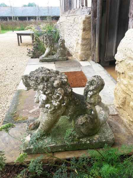A pair of characterful seated stylised Bath stone dogs