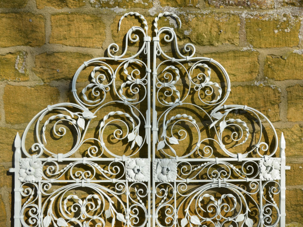 A pair of ornate wrought iron garden gates
