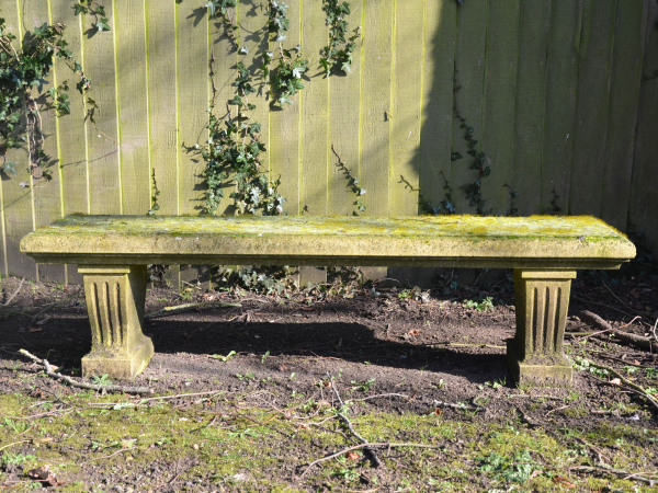 A weathered carved natural limestone garden bench