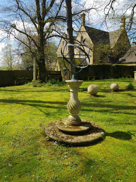A weathered hand carved natural limestone sundial of baluster form