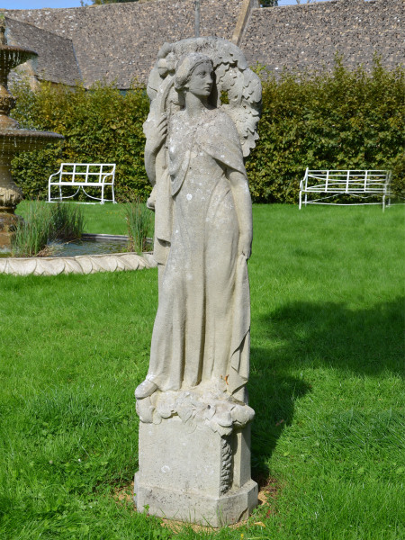 A carved stone niche figure in the Arts and Crafts style depicting an allegory of Autumn