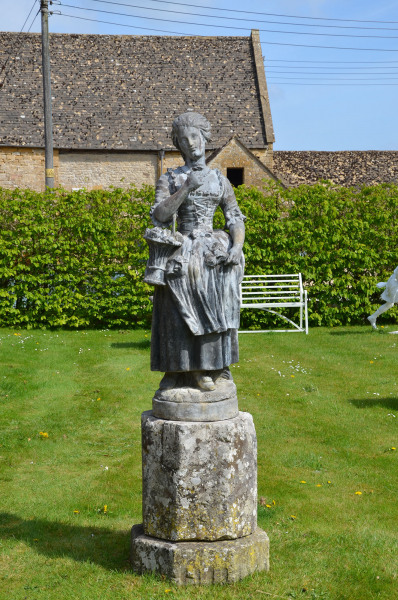 A large lead figure depicting a flower girl