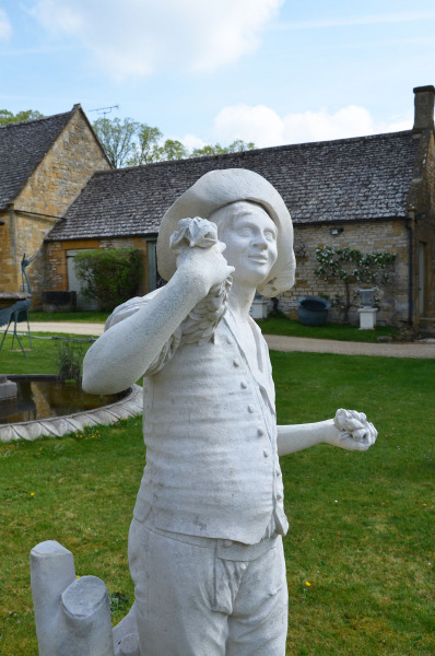 A French carved Caen stone figure of a grape picker