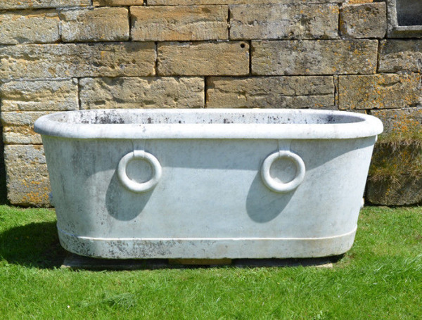 A carved white marble cistern of elongated oval form