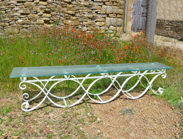 A 20th century iron bench with frosted glass seat