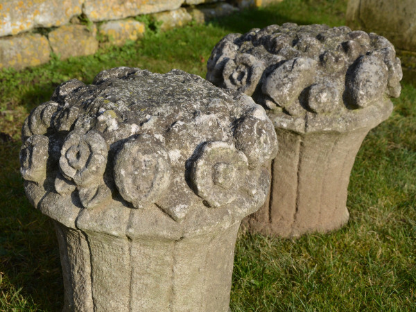 A pair of carved Portland stone fruit and flower baskets