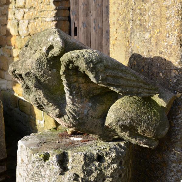 A large medieval carved limestone long fingered mouth puller gargoyle