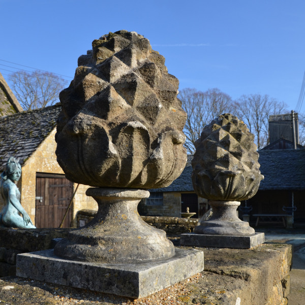 A pair of carved Bath stone pineapple finials