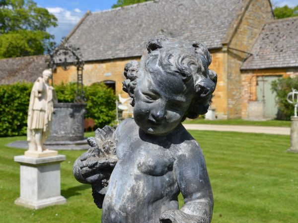 An early 20th century lead garden figure in the form of a cherub