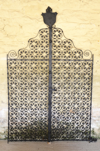 A pair of early 20th century wrought iron garden gates with shield